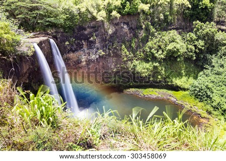 Beautiful Opaekaa Falls in Kauai Hawaii forms a rainbow when the sun angle contacts mist at the right time of day.W - stock photo