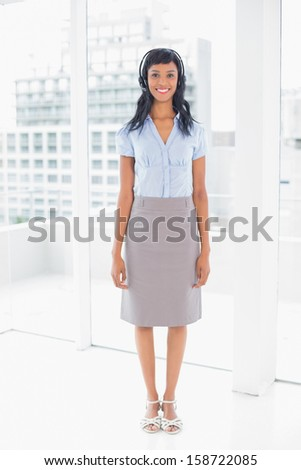 Beautiful operator smiling and looking at camera in office - stock photo