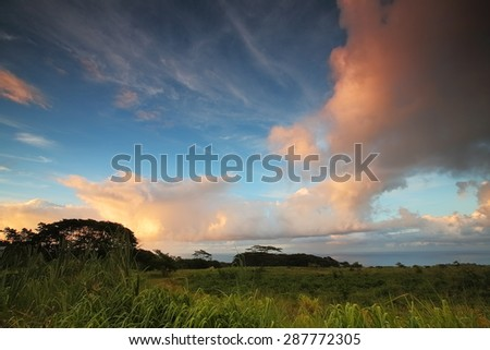 Beautiful orange clouds above grassland fields on the big island of Hawaii - stock photo