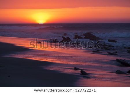 Beautiful orange purple sunset on the beach of Punta Sal, near Mancora, Peru. - stock photo