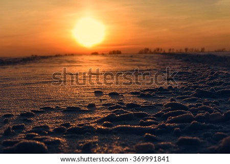 Beautiful orange sunset with a large sun and the reflection of sunlight on the snow in a field in the winter - stock photo