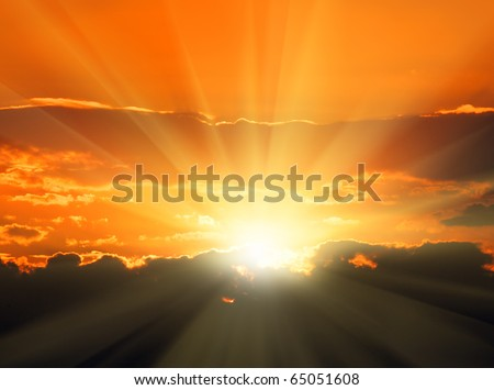 beautiful orange sunset with sunbeams and dark clouds - stock photo
