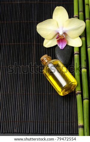 Beautiful orchid and parfume bottle with thin grove o black - stock photo