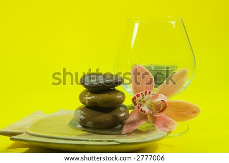 Beautiful orchid in fish shaped shallow container, with water running over stones in front of a large brandy glass containing a green candle and cheerful yellow background with lots of copy space - stock photo