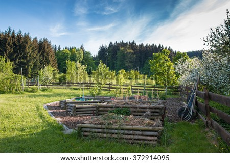 beautiful organic garden on the orchard with wooden vegetable beds and compost in the spring - stock photo