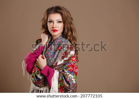 beautiful oriental look young woman with scarf on green background. portrait of a beautiful young woman with a scarf on her shoulders. Russian beauty. Russian national traditional scarf. Studio shot  - stock photo