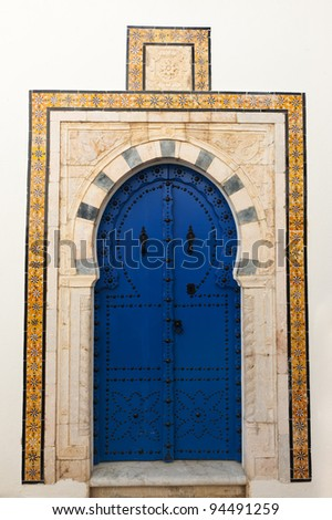Beautiful ornamental blue door of so typical shape for Tunisia - stock photo