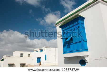 Beautiful ornamental blue windows on a white wall so typical for Tunisia - stock photo