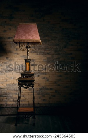 Beautiful ornate stand lamp in empty room. Nice play of shadows on the wall - stock photo