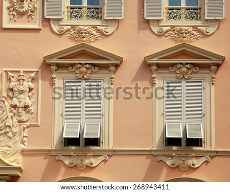 Beautiful ornate stucco house with old french grey shutter windows in Principality of Monaco, Monte Carlo. - stock photo