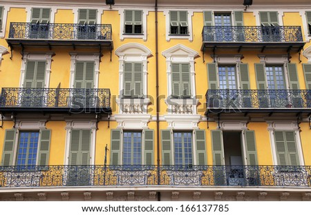 Beautiful ornate yellow building facade with balcony and traditional green shutter windows,Nice,Cote d'Azur, France. - stock photo