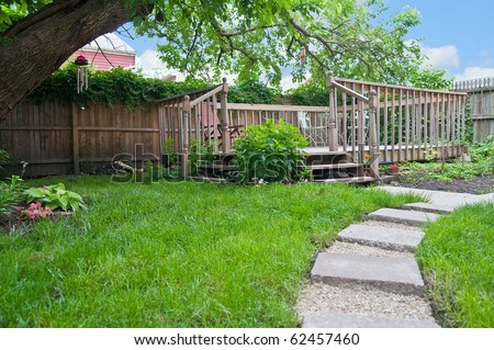 Beautiful outdoor deck seating area in the back yard garden provides restful relaxation and solitude. - stock photo