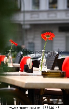 Beautiful outdoor summer restaurant tables and chairs with red flowers in vases