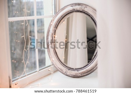 beautiful oval mirror on the windowsill with garlands