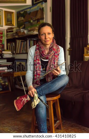 Beautiful painter sitting painting in a studio or gallery holding a colorful artists palette and paintbrush in her hand and smiling - stock photo