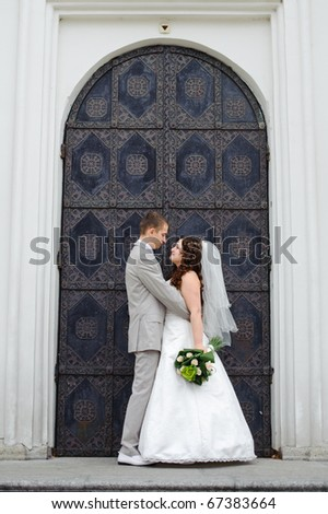 beautiful pair of newlyweds is against the background of forged metal door to the temple face to face