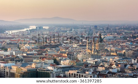 Beautiful Panorama Aerial view of St. Stephen's Basilica Big dome above sunny buildings, Ferris wheel and rooftops under Golden Sunset at Dusk in Summer evening, Budapest - stock photo