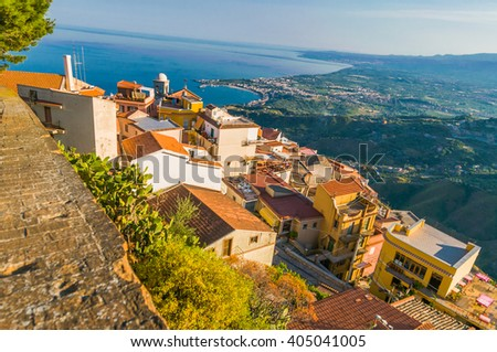 Beautiful panorama from mountain top to a small mediterranean sicilian town, Taormina, in warm sunset with the sea in the background, Sicily, Italy - stock photo