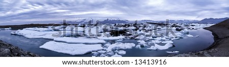 beautiful panorama scenery with a floating icebergs in the foreground and a glacier in the background; Jökulsárlón; Iceland - stock photo