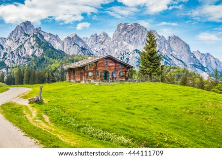 Beautiful panorama view of idyllic rural mountain scenery in the Alps with traditional old alpine mountain hut and fresh green meadows on a sunny day with blue sky and clouds in springtime - stock photo