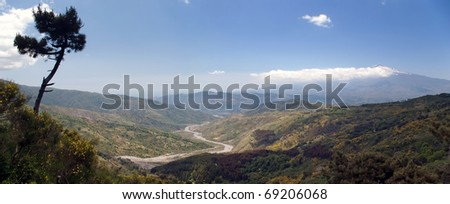Beautiful panoramic valley of the sicilian hinterland under the majestic volcano Etna with dry river bed - stock photo