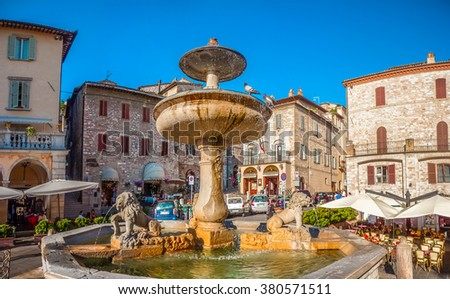 Beautiful panoramic view of famous Piazza del Comune with historic fountain figuring three lions and ancient palaces in the background on the main sqaure of Assisi, Umbria, Italy - stock photo