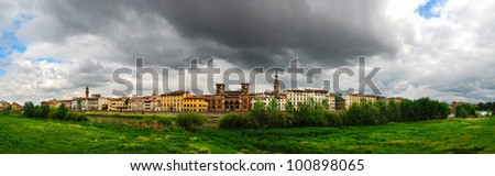 Beautiful panoramic view of Florence, Arno River, National Library in the middle and with majestic powerful clouds. - stock photo