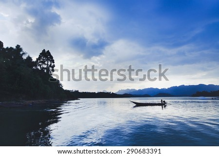 beautiful panoramic view of lake with boat of fisherman - stock photo