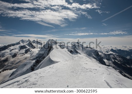Beautiful panoramic view of summer landscape around Breithorn in Pennine Alps with cloudy blue sky.