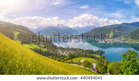 Beautiful panoramic view of the famous city of Zell am See with idyllic Zeller Lake and blooming meadows on a sunny spring day in Salzburg, Salzburger Land, Austria - stock photo