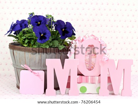 Beautiful pansys in a rustic basket, gifts, a gift card and Mom spelled out in wooden letters.  Great for Mom's birthday or Mothers Day. - stock photo