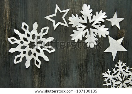 Beautiful paper snowflakes on wooden background - stock photo