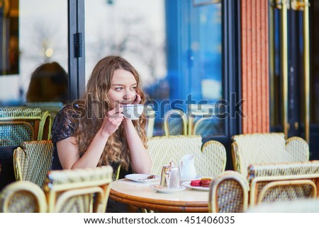Beautiful Parisian woman in cafe, drinking coffee and eating macaroons, traditional French dessert
