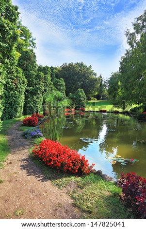 Beautiful park in northern Italy Sigurta. Picturesque bush with red flowers around a circular pond - stock photo