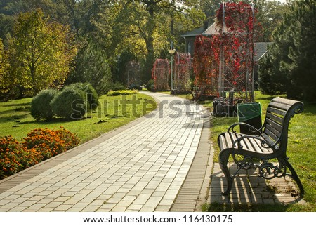 Beautiful park with pathway, arbors and benches - stock photo