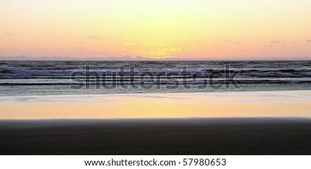 Beautiful pastel yellow sunset on sandy ocean beach - stock photo