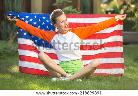 Beautiful patriotic young woman with American flag held in her outstretched hands sitting on green grass - stock photo