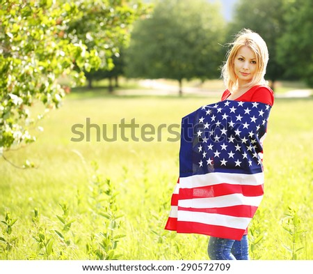 Beautiful patriotic young woman with American flag. Outdoor