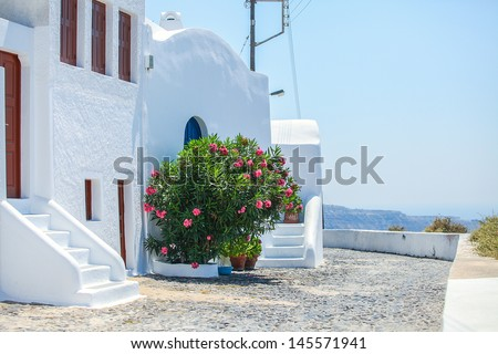 Beautiful paved street with old traditional white house in Fira, Santorini, Greece - stock photo