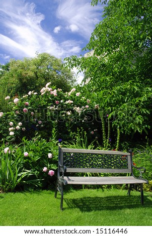Beautiful peaceful garden with a bench surrounded by pink roses - stock photo