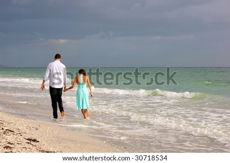 beautiful peaceful image of young couple walking along bonita beach in bonita springs florida on the gulf of mexico as the sun begins to set behind them - stock photo