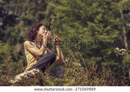 Beautiful peaceful redhead woman gently touching and smelling wild mountain plants. - stock photo