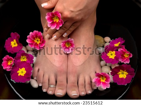 Beautiful pedicured feet and manicured hand with colorful spring flowers in a spa - stock photo