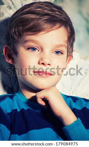Beautiful pensive boy with blue eyes - stock photo