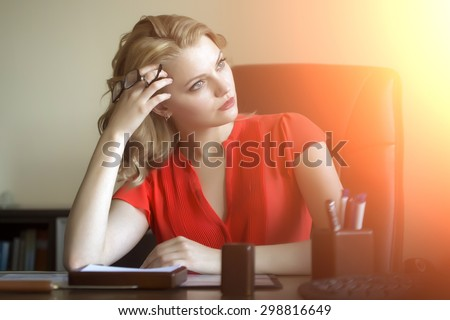 Beautiful pensive elegant blond business woman sitting in office on brown leather chair in red blouse holding glasses in hands looking away indoor on white background with flash, horizontal picture - stock photo