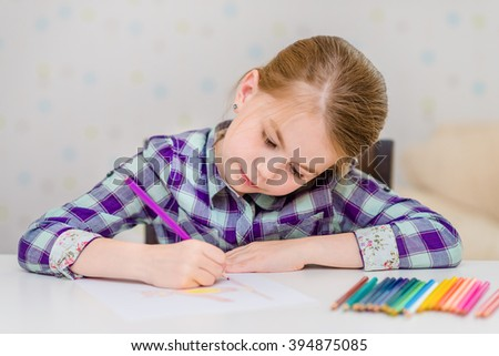 Beautiful pensive little girl with blond hair sitting at white table and drawing with multicolored pencils - stock photo
