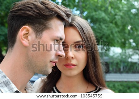 Beautiful pensive man and woman stand in park; green trees; focus on woman - stock photo