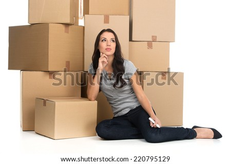 Beautiful pensive woman during move with boxes at new flat. young woman holding marker while sitting and thinking in new apartment - stock photo