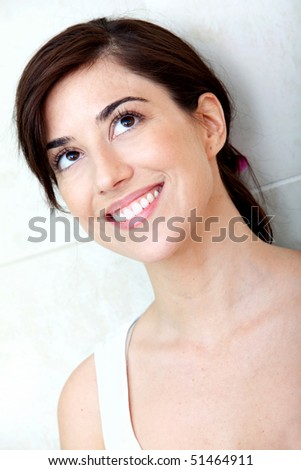 Beautiful pensive woman looking up and smiling - stock photo