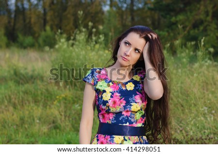 Beautiful pensive woman with long hair standing in a forest glade on a summer evening - stock photo